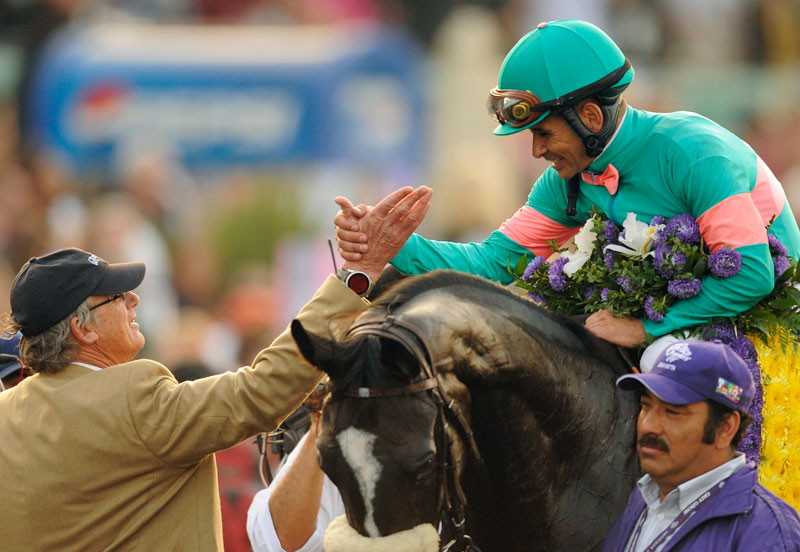 Zenyatta and jockey in teal and pink silks.